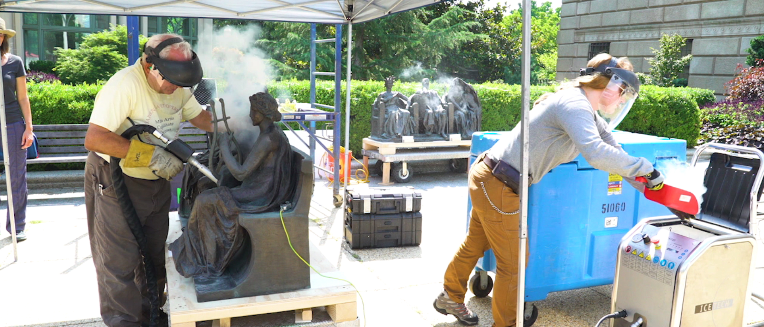 two conservators with face shields ice blasting sculptures
