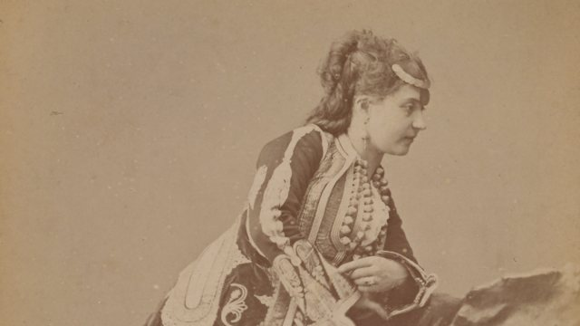 sepia photograph of a woman with an elaborately decorated dress leaning over a stone, wearing a metal hair ornament