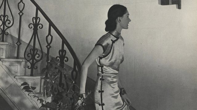 a woman in a silk dress descending a spiral staircase