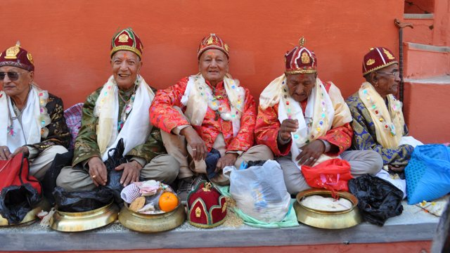 five elderly men in dark red hats and bright performance outfits