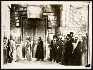 Well-dressed religious dignitaries gather outside a pair of ornate doors