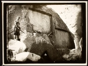 A man with a bayonet stands sternly next to Sassanid Inscriptions of Ganj-Nama carved into the face of a cliff