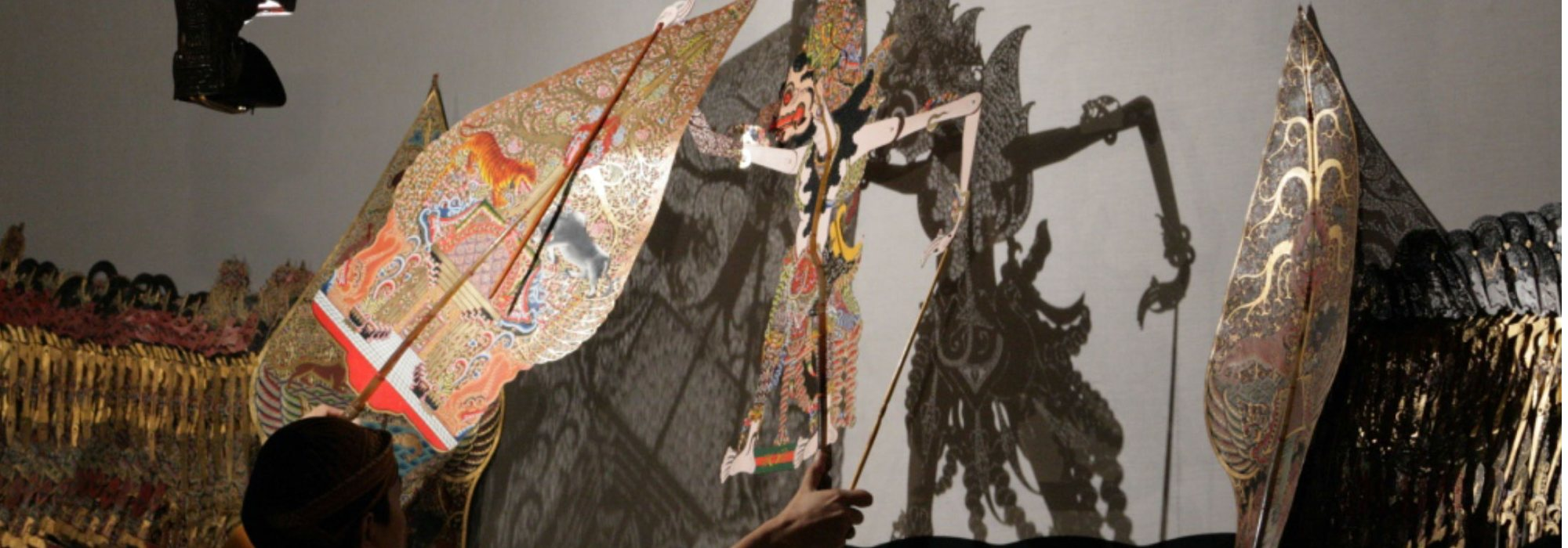 Shadow puppet made of intricately cut paper being controlled by puppeteer.