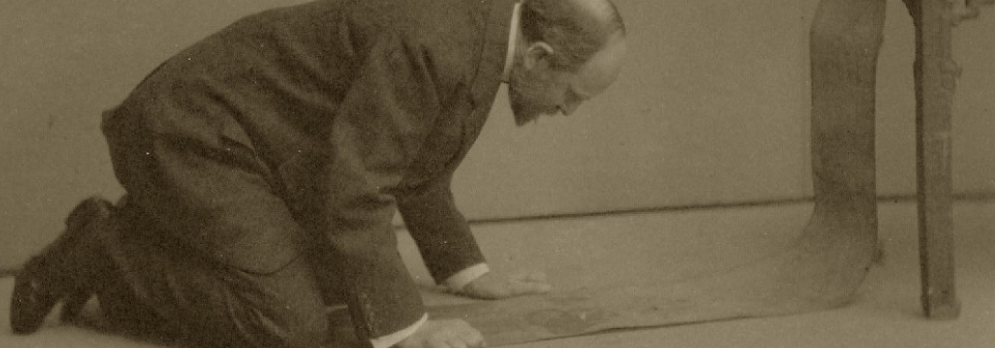 Photograph of Charles Lang Freer kneeling on the floor to examine a scroll, by Alvin Lang Coburn.