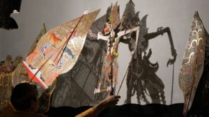 Shadow puppet made of intricately cut paper.