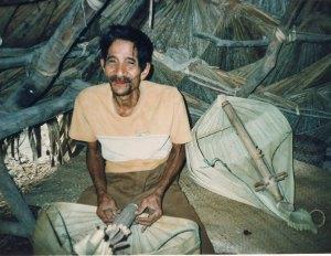 A man seated on the floor playing sasando biola