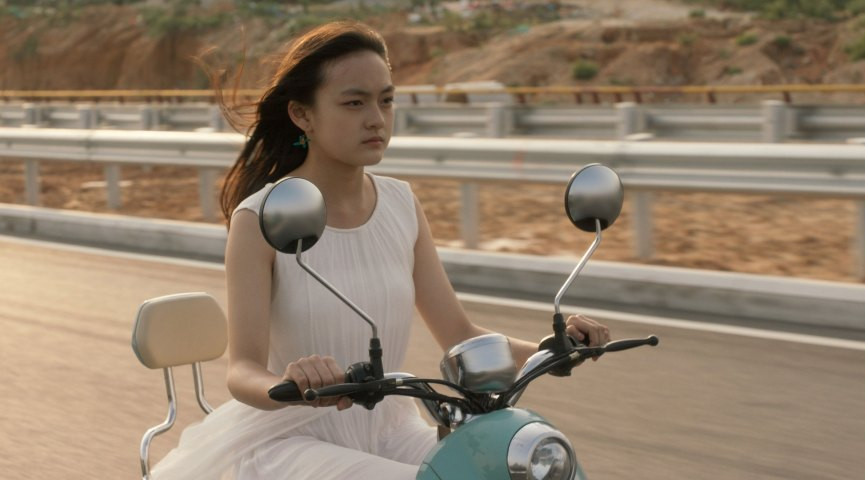 Girl in a dress with a somber expression, riding on a motor scooter