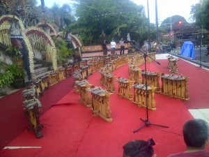 Fifty gender wayang set up on an empty outdoor stage, gold contrasting against the red carpeted ground.