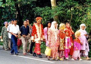 Wedding procession lead by individuals in colorful traditional garments in red, gold, and pink.