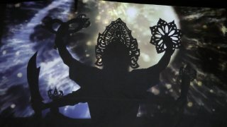 The silhouette of a six armed figure, in front of an abstract, projected background.