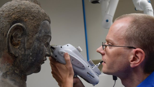 conservator using XRF gun to examine pupil of a Buddha statue