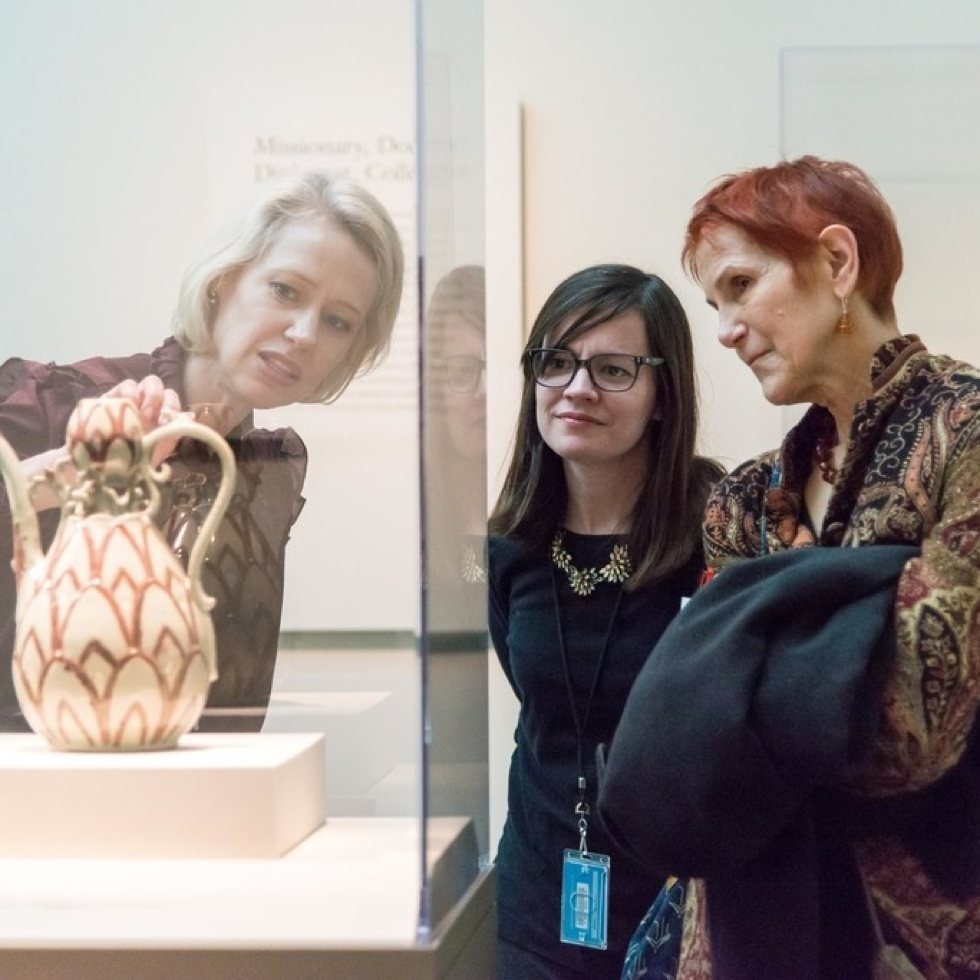 three women viewing a vase in a case