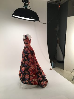 a white female mannequin wearing a vivid floral patterned dress in the middle of a photo shoot setting