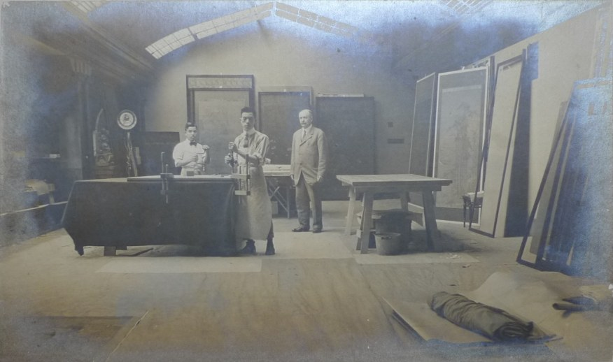three men in suits standing behind a table in large hall