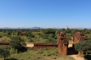 Brick ruined gate with stupas and mountains in the green landscape beyond