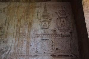 Lightly drawn stucco walls showing a Buddha in a stupa
