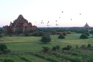 Hot air balloons rising with the sun beside a red temple, in a landscape of paddy fields