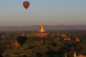 Golden stupa at sunrise with a hot air balloon in the sky