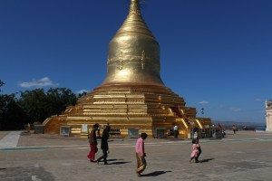 A gleaming golden stupa with worshippers circumambulating