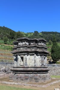 Flat shrine with green hills behind