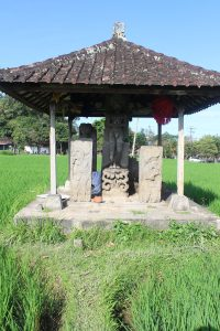 Hut-shaped single shrine in rice fields, with sculptures inside