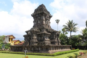 Tall temple tower in green lawn, with sculptures to the side