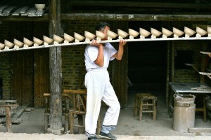 Man carrying a rack with many bowls on his shoulder
