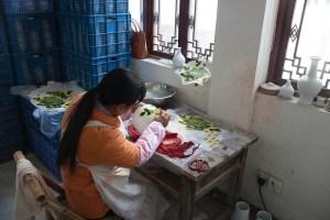 Woman applying applique designs to a teapot
