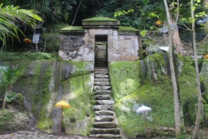 In the jungle, a flight of rock-cut stairs leading up to a gate and shrine complex, with yellow and white umbrellas