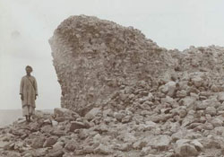 man standing next to rock formation