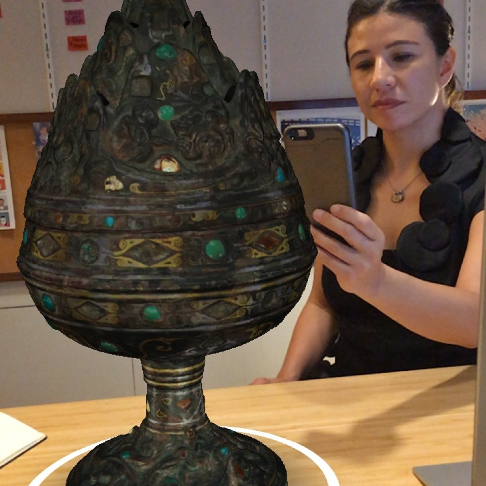 female holding a phone in front of a 3D image of a large incense burner