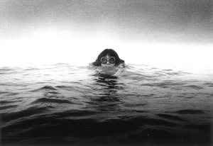 black and white photo of a woman swimming, her head above the water and wearing round goggles