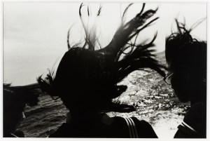 black and white photo of a silhouette of a girl with her hair flying in the wind