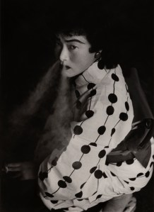 black and white photo of a person wearing makeup and blowing smoke from their nose