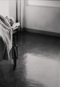 A black and white photo of a man on a bed in a room