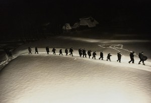 black, white and sepia-toned image with several individuals walking in a line through the snow