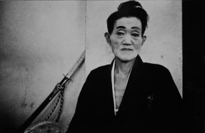 a black and white photo of a figure in facepaint and a kimono, a sword leaned up against a wall behind them