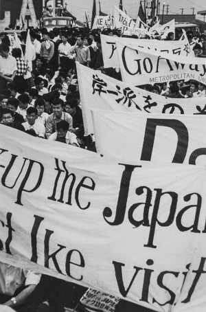 black and white photo of a crowd of people carrying banners with protest text