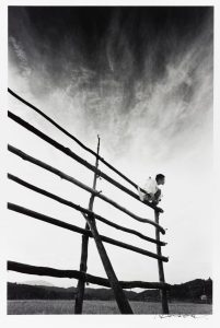 black and white photo of a wooden fence with a man sitting on one end, a stormy sky fading from dark to light in the background