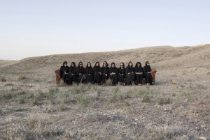 eleven women dressed in black seated on a long wooden bench in hilly field
