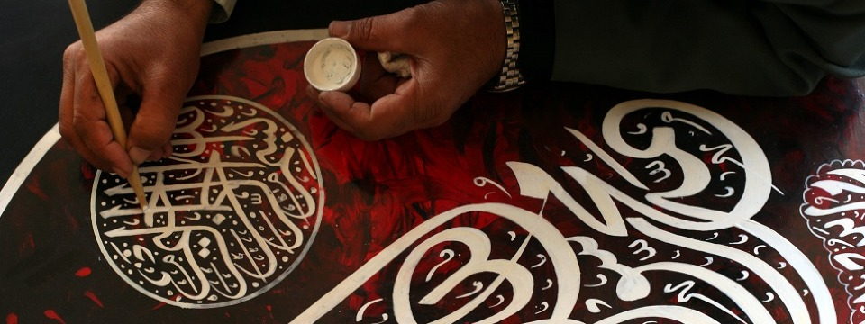 Artists' hand brushing calligraphy in white on red.