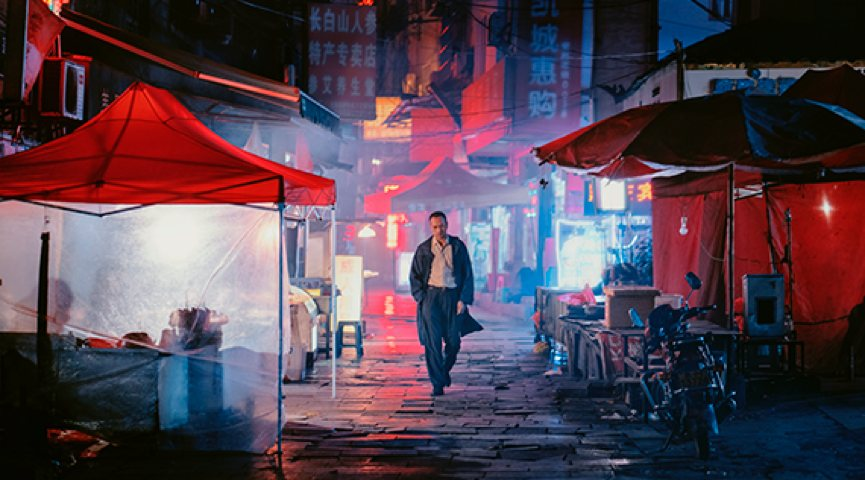man walking through night market