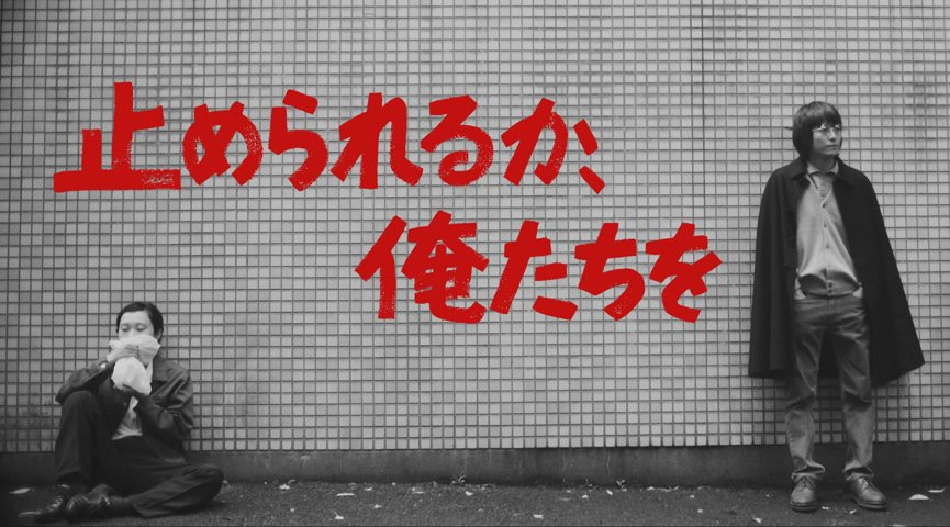 a black and white photo of a seated female and standing male in front of a white brick wall with bright red japanese characters between them