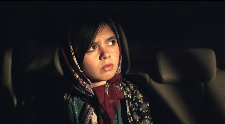 still from the film Faces, a women in a vehicle, her face luminous against the shadow, wearing a burgundy headscarf and a dark coat