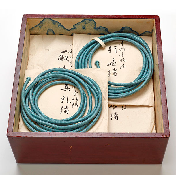 Red lacquer tray containing teal cotton cord, neatly looped for storage.