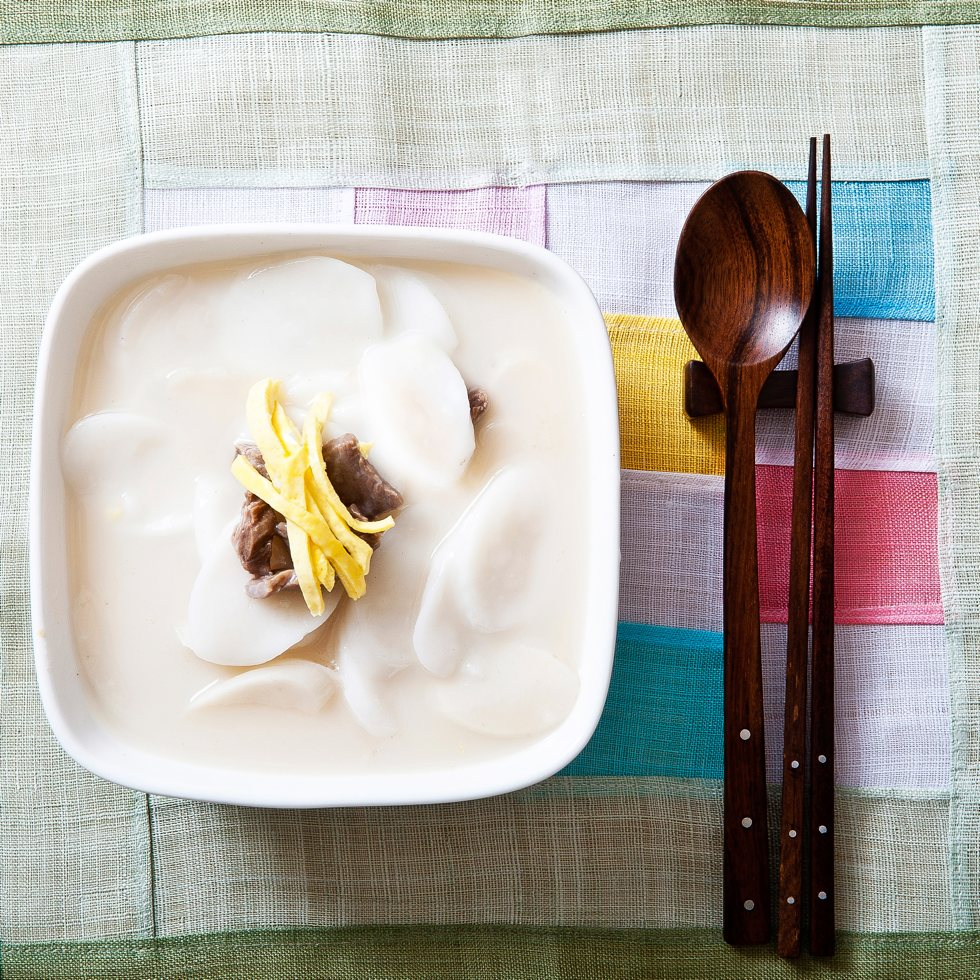 bowl of tteokguk (rice cake soup) on pastel-colored placemat and wooden spoon and chopsticks