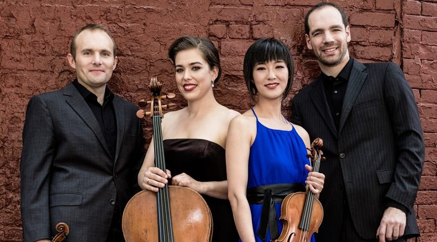 four musicians (two males and two female) standing against red brick wall, holding string instruments