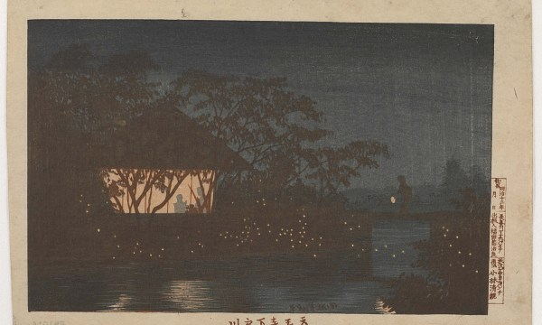 A small structure, lit from within with warm light is nestled within trees on the bank of the Koromogawa River.