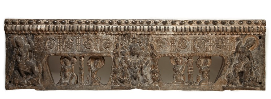 carved brown stone showing figures and divinities