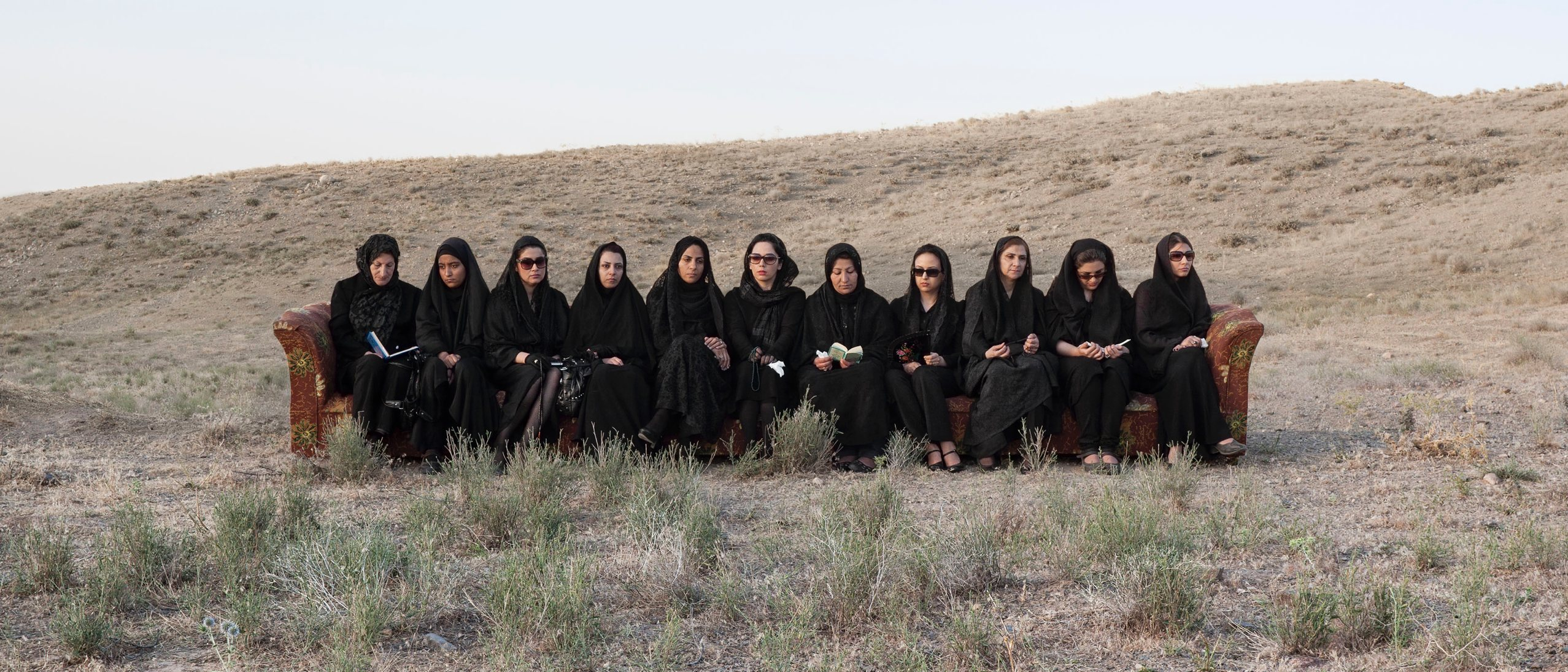 eleven women in all black seated on a long sofa in the middle of an arid field